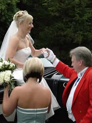 English toastmaster Richard Palmer assisting the bride from a horse drawn carraige at St Mary's Church, Great Baddow, Essex